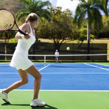two people playing tennis in a tropical setting